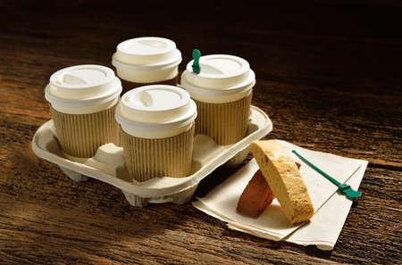 Papieren kopjes koffie en biscotti op houten achtergrond