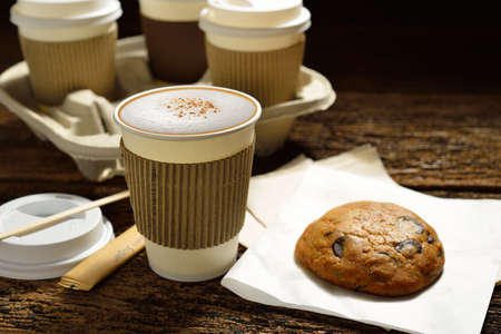 take away: Paper cups of coffee and cookie on wooden background