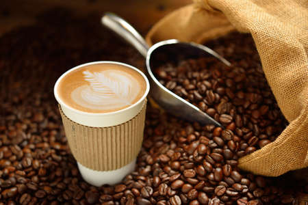 Paper cup of coffee latte and coffee beans on wooden table Stockfoto