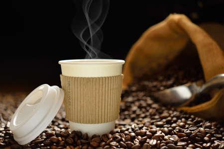 Papieren kopje koffie met rook en koffie bonen op houten tafel