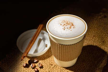 capuchinos: Taza de papel de café y granos de café en la mesa de madera
