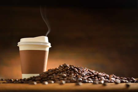 Paper cup of coffee with smoke and coffee beans on old wooden background