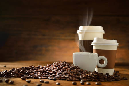 coffee table: Cups of coffee with smoke and coffee beans on old wooden background Stock Photo