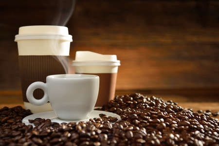 Cups of coffee with smoke and coffee beans on old wooden background Stock Photo