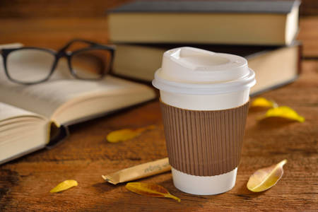 to go cup: Paper cup of coffee and books on wooden table