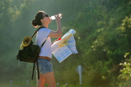 Woman tourist with backpack drinking water in nature