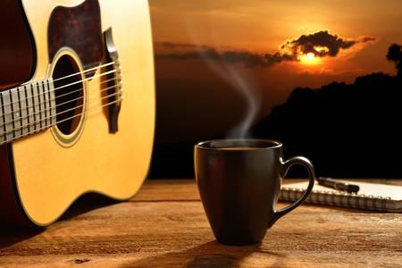Tasse Kaffee und Gitarre mit der Sonne im Hintergrund Standard-Bild