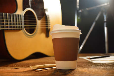 take a break: Paper cup of coffee and guitar on wooden table