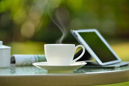 Kopje koffie met rook en tablet-computer in de tuin