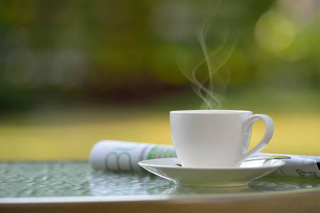 Cup of coffee with smoke and newspaper in garden Stock Photo