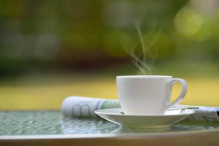 Kopje koffie met rook en een krant in de tuin Stockfoto