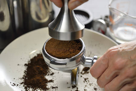 tamper: Barista using a tamper to press ground coffee into a portafilter