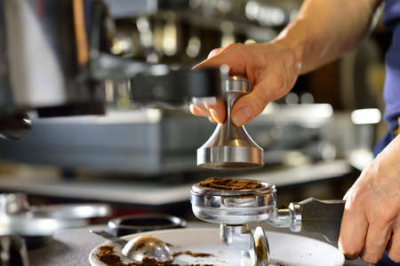 Barista using a tamper to press ground coffee into a portafilter