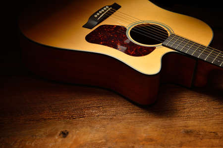 Acoustic guitar on old wooden background