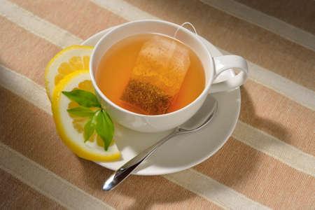 Cup of tea with tea bag and lemon on table Stock Photo