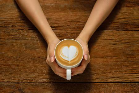 ハート型に、コーヒーのカフェラテのカップを保持している女性 写真素材
