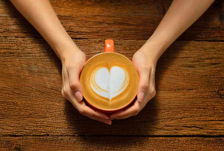 taza de café: Mujer que sostiene la taza de café con leche, con forma de corazón