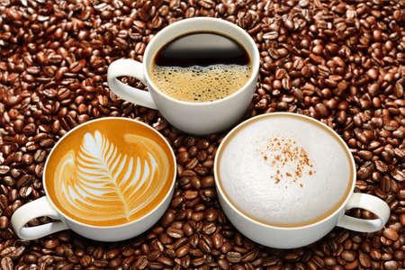 Vielzahl von Tassen Kaffee auf Kaffeebohnen Hintergrund