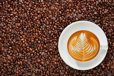 コーヒー豆の背景にコーヒー カフェラテのカップ