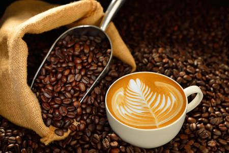 一杯のコーヒーのカフェラテと木製のテーブルの上のコーヒー豆 写真素材