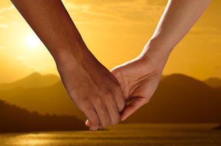 держась за руки: Пара, держась за руки, наблюдая красивый закат Фото со стока