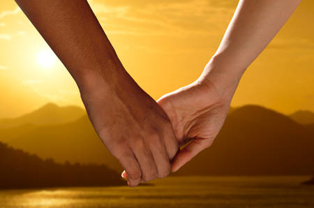 holdings: Couple holding hands watching a beautiful sunset Stock Photo