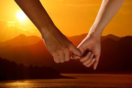 cogidos de la mano: Pareja de la mano mirando una hermosa puesta de sol