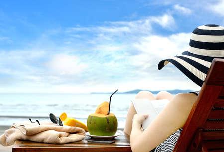 ビーチで本を読む若い女性