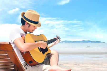 ビーチでアコースティック ギターを弾く若い男