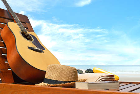 Guitar,hat,book and beach accessories on a beach chair with sea background Banque d'images