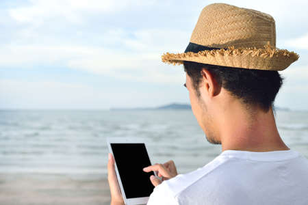 relaxing beach: Man relaxing and use tablet computer at beautiful tropical beach