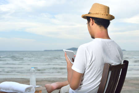 man with laptop: Man relaxing and use tablet computer at beautiful tropical beach