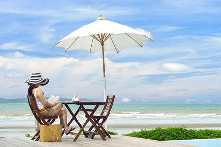 personas leyendo: Joven mujer leyendo un libro en la playa