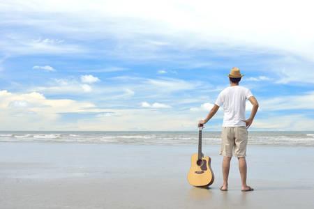 cielo azul: Hombre joven con una guitarra acústica en la playa
