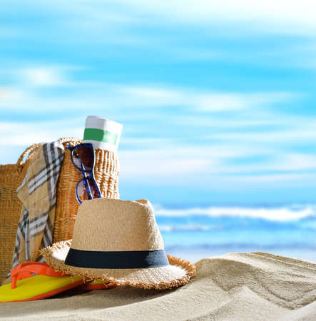 Beach accessories on sandy beach with blue sea and sky background Imagens