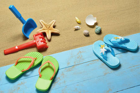 flip flops: Childrens flip flops with beach toys and sea shells on the sandy beach
