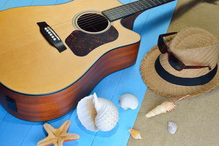 concert background: Acoustic guitar with starfish and seashells on the beach
