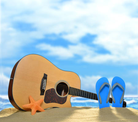 Acoustic guitar and flip flops on the sandy beach in summer with blue sea and sky