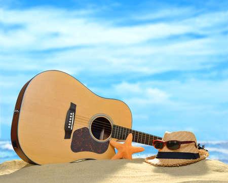 gitara: Gitara akustyczna na piaszczystej plaży w lecie z niebieskim morzem i niebem Zdjęcie Seryjne