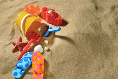 Children's flip flops with beach toys and sea shells on the sandy beach