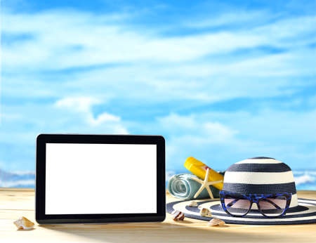 Tablet computer beach accessories and sea shells on the beach with blue sea and sky