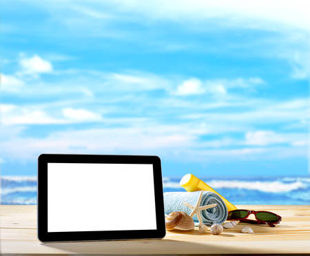 Tablet computer and beach accessories on sandy beach with blue sea and sky