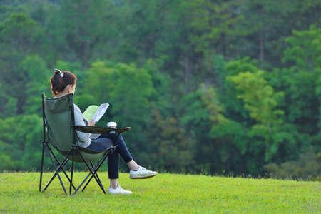 Jonge vrouw zittend op camping stoel lezen van een boek in het park Stockfoto