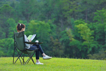Young woman sitting on camping chair reading a book in the park Imagens