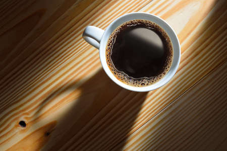 cup: Top view of a cup of coffee in the morning light on wooden background Stock Photo