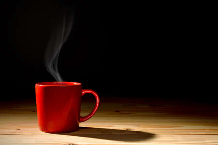 Cup of coffee with smoke on old wooden background