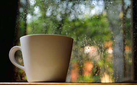 Cup of coffee on a rainy day window background
