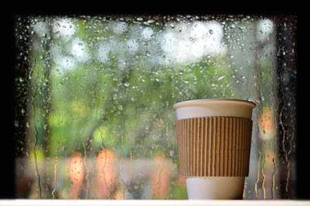 Paper cup of coffee on a rainy day window background