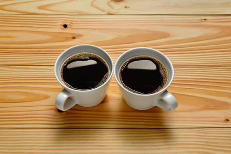 two on top: Top view of two cups of coffee on wooden background