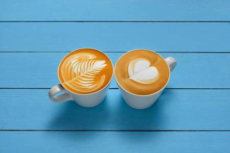 capuchino: Arte Latte, tazas de café con leche en el fondo de madera Foto de archivo